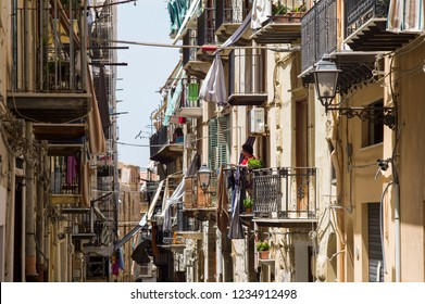 Cefalu, Italy - July 5 2017: The resident is resting at balcony in the narrow street of old town Cefalu in Sicily.