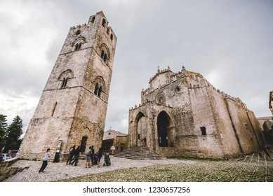 CEFALU, SICILY / ITALY - OCTOBER 6, 2018: People walking around cathedral of Erice town and its tower