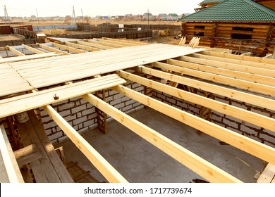 Ceiling beams are made of natural eco-friendly materials. Elements and components of the construction of roof. Construction of a country one-story house