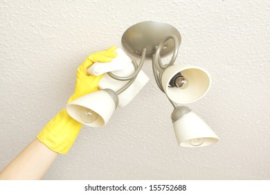 ceiling light fittings with a woman's hand cleaning them with a cloth