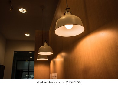 Ceiling lighting fixture lamps hanging along the curved of wooden wall in modern cafe