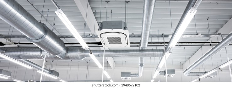 Ceiling mounted cassette type air condition units with other parts of ventilation system (tubes, cables and vents) located inside commercial hall with hanging lights and other construction parts.