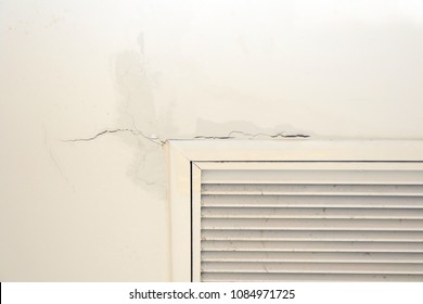 Ceiling panels in livingroom roof with water drop from air conditioner drain pipes leaking. Broken and wet on ceiling house problem concept.