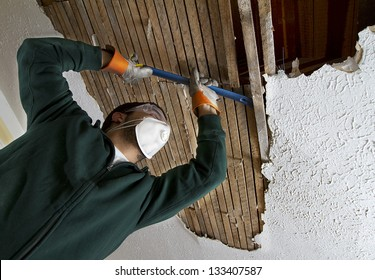 Ceiling Repair view from below. man removing plaster lathe from ceiling.