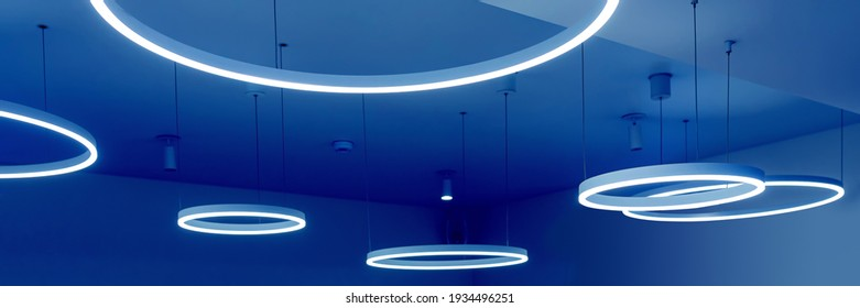Ceiling with round modern LED lamps. Suspended fluorescent lights under the ceiling. Careful energy consumption, energy saving concept. Banner