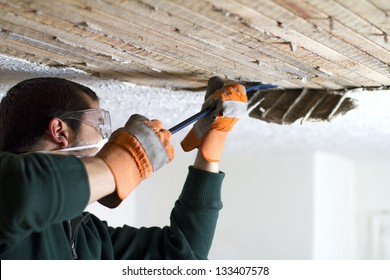 Ceiling Scrape man scraping plaster off of ceiling lathe with a crowbar