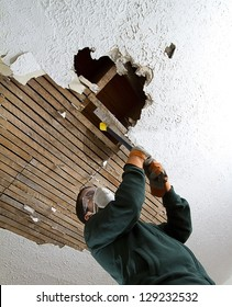 Ceiling Take Down vertical shot from below of a man pulling down plaster ceiling lathe with a crowbar. large hole in ceiling.