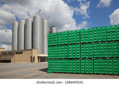 CELAREVO, SERBIA - JUNE 11. 2017. Carlsberg Serbia brewery, heap of green crates for Tuborg beer  at large warehouse with storage tanks and factory in background
