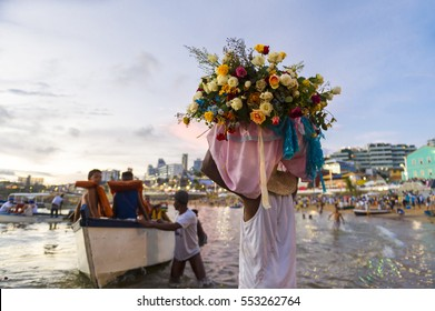 A celebrant at the Festival of Yemanja carries flowers to a boat to leave as an offering at sea on Rio Vermelho beach in Salvador, Brazil