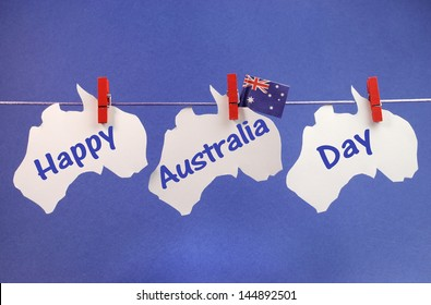 Celebrate Australia Day holiday on January 26 with a Happy Australia Day message greeting written across white Australian maps and flag hanging pegs on a line against a blue background.