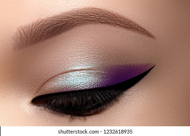 Celebrate Beautiful Macro Eyes with Smoky Cat Eye Makeup. Cosmetics and Make-up. Closeup of Fashion Visage with Liner, Purple and Cyan Eyeshadows.