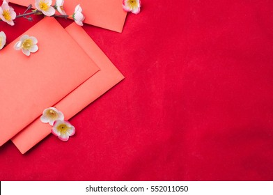 celebrate Chinese New Year background with red envelope and beautiful blossom.