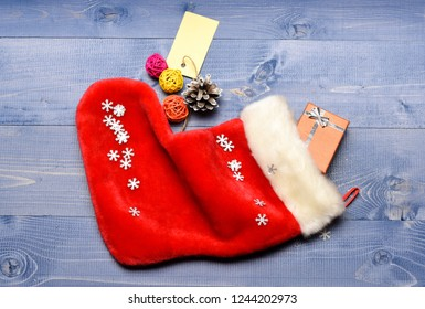 Celebrate christmas. Contents of christmas stocking. Small items stocking stuffers or fillers little christmas gifts. Christmas sock toned wood background top view. Fill sock with gifts or presents.