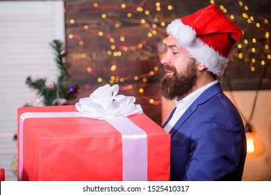 Celebrate christmas with giant gifts. Big wrapped box with ribbon. Great surprise. Prepare huge surprise gift. Man santa claus hat carry big gift box. Size matters. Biggest gift for christmas.