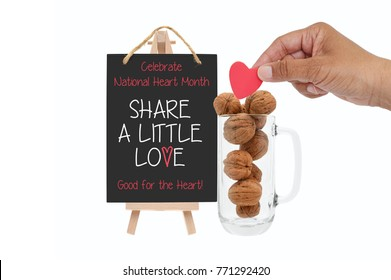 "Celebrate February National Heart Month ""Share A Little Love"" Good for the Heart Blackboard Sign next to glass mug of walnuts and hand holding heart white background"