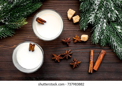 Celebrate new year winter evening with eggnog drink in glasses. Vanilla, spruce branch and cinnamon . Wooden desk background top view
