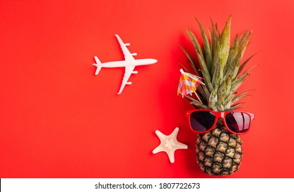 Celebrate Summer Pineapple Day Concept, Top view flat lay of funny fresh pineapple wear red sunglasses with model plane and starfish, isolated on red background, Holiday summertime in tropical