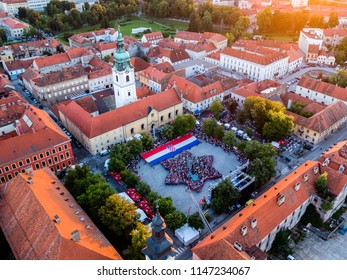 Celebrating birthday of Karlovac city with millennial photo of Karlovac star outline and big Croatian flag with sun flares and Karlovac church in background, aerial photo with drone
