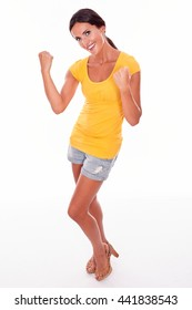 Celebrating brunette woman gesturing with fists up in front while looking at camera and wearing a yellow t-shirt and short jeans isolated