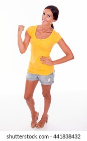Celebrating brunette woman gesturing with one fist up in front while looking at camera and wearing a yellow t-shirt and short jeans isolated