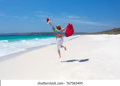 Celebrating Christmas in Australia, hot sunny days and lazy days down at the beach.  A woman celebrates jumps for joy on  white sandy beach.  Christmas celebration, Christmas vacation, copy space