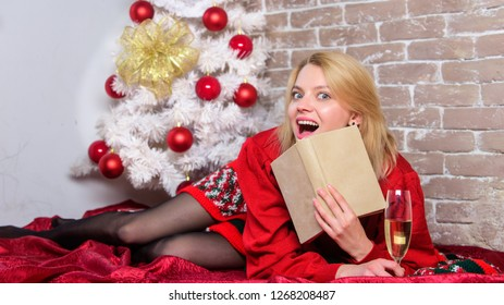 Celebrating christmas as introvert. Celebrate christmas without social obligations. Woman hold glass champagne and book. Girl relax near christmas tree. Alone on christmas. Holiday tips for introvert.