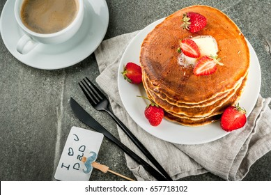 Celebrating Father's Day. Breakfast. The idea for hearty and delicious holiday breakfast: pancakes with butter, maple syrup and fresh strawberries, with congratulations. Coffee cup. Copy space
