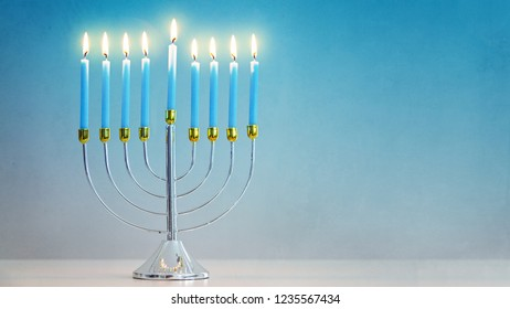 Celebrating Hanukkah with illuminated candles in silver and gold menorah on table with room for text in blue background