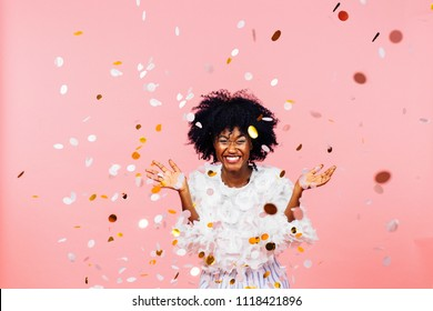 Celebrating happiness, young woman with big smile throwing confetti