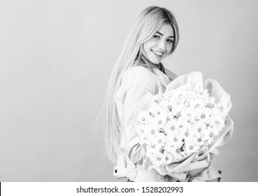 Celebrating her special day. Surprise for girlfriend. Adore flowers. Girl tender sensual blonde hold flowers bouquet. Flowers delivery service. Chamomile flower symbol of innocence and tenderness.