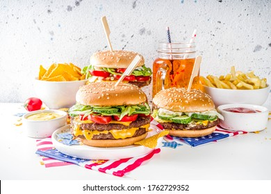 Celebrating Independence Day, July 4. Traditional American Memorial Day Patriotic Picnic with burgers, french fries and snacks, Summer USA picnic and bbq concept, White concrete background
