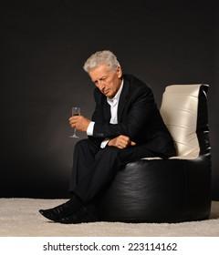 Celebrating mature businessman sitting in armchair on black background