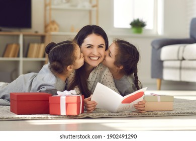 Celebrating Mothers day or Womans day at home concept. Happy young mother woman lying on floor between kissing her daughters and reading handmade postcard for mom on holiday - Shutterstock ID 1902491290