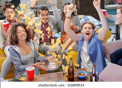 Celebrating multi racial group of sports fans student friends sharing snacks celebrating winning goal for season drinking beer throwing chips celebrating sport match