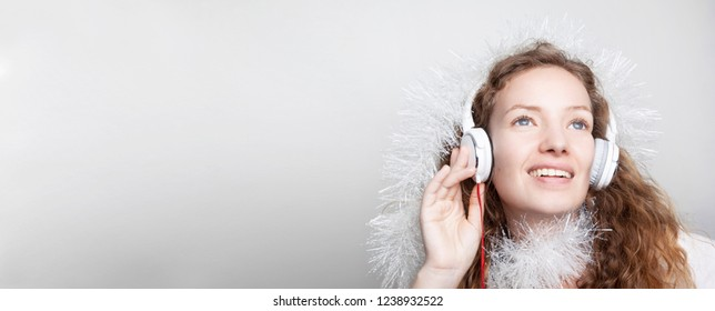 Celebrating New Yea. Young woman with headphones listening to music. Christmas and New Year songs