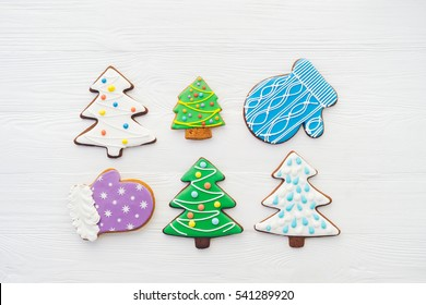 Celebrating New Year at home. Christmas ginger and honey cookies on white wooden background. Fir tree, glove shape. Festive bakery top view, flat lay. Gingerbread with copy space.