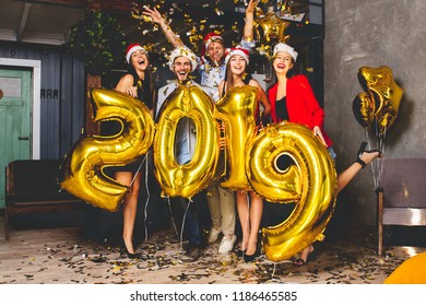 Celebrating New Year party. Group of cheerful young girls in beautiful wearing carrying gold colored numbers 2019 and throwing confetti
