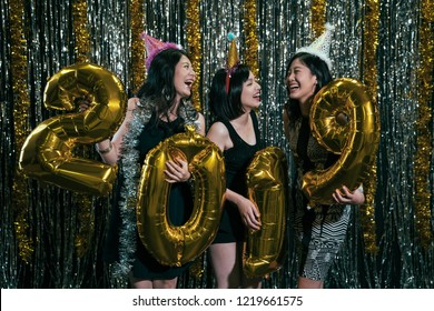 Celebrating New Year party group of cheerful young girls wearing dresses carrying gold colored numbers 2019 balloon. attractive beautiful ladies chatting night dico club. joyful friendship night out.