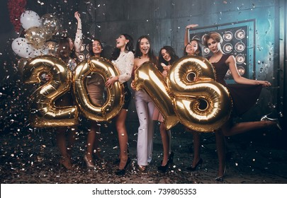 Celebrating New Year party. Group of cheerful young girls in beautiful wearing carrying gold colored numbers 2018 and throwing confetti