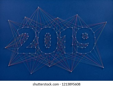 Celebrating the new year together. Colorful network of pins and threads in the shape of the year 2019 symbolising community and team effort in building the future.