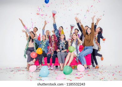 Celebrating New Year together.Group of young people in hats throwing colorful confetti and looking happy at office.