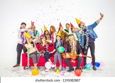Celebrating New Year together.Group of young staff people in hats throwing colorful confetti and looking happy at office.