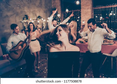 Celebrating newyear. Beautiful lady in motion, hair in the air, group of festive youth on fancy feast, many glitters confetti on floor, classy outfits, chilling relax mood all night, indoors event