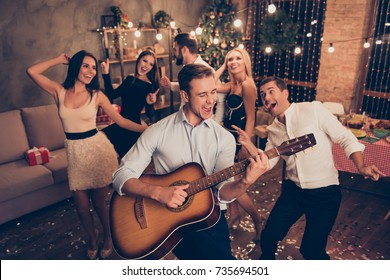 Celebrating newyear. Young handsome musician makes a noise with his instrument! Group of beautiful festive youth on luxury feast, many glitters on floor, classy outfits, Chilling relax mood all night