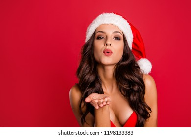 Celebrating noel party with lover. Brunette delicate, winsome, lady with curly wave modern hairdo send kiss from open palm look at camera isolated on vivid red background with copy space for text