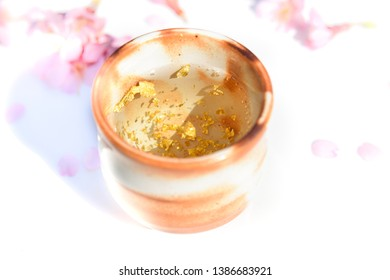 celebrating sake with golden leaf in white background with cherry blossom