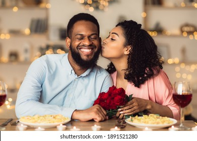 Celebrating Special Day. Beautiful black girlfriend kissing her smiling boyfriend in cheek, holding bouquet of red roses. Couple sitting at table in luxury restaurant during romantic date and dinner
