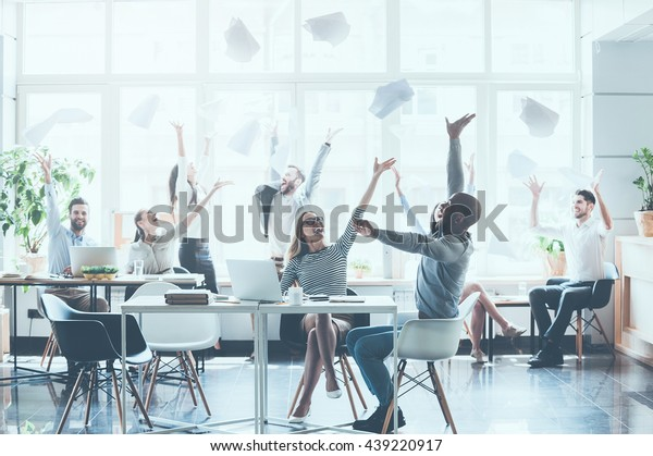 Celebrating success. Group of young business people throwing documents and looking happy while sitting at their working places in office
