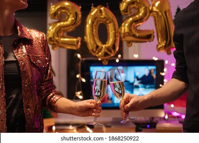 Celebrating Virtual Christmas New Year's Eve party 2021 at home during Covid-19 pandemic. Couple holding and toasting champagne glasses How to celebrate and decorate foiled balloons of 2021.  - Shutterstock ID 1868250922