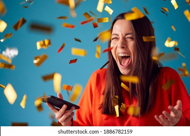Celebrating Young Woman With Mobile Phone Winning Prize And Showered With Gold Confetti In Studio